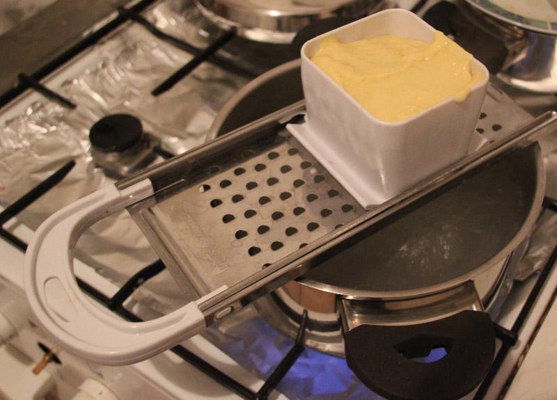 teig in spätzlereibe über kochendem wasser