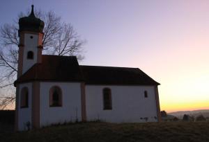 wallfahrtskapelle volkertshaus im sonnenuntergang mit baum